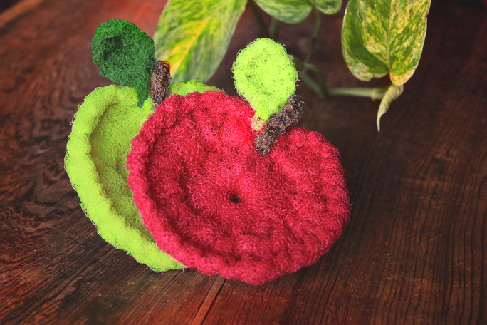 red and green apple scrubbies with wood and leaf background