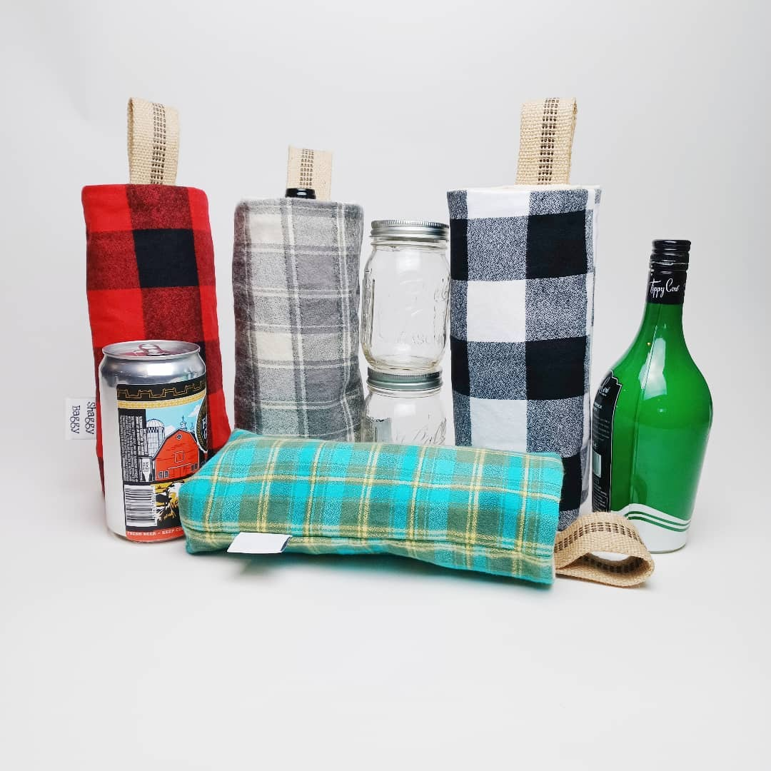 shaggy baggy totes in buffalo plaid, red and white, grey and whit, blue and yellow and a green bottle